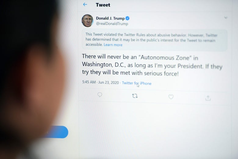 A person looks at a tweet from Donald Trump that is flagged with a notice from Twitter saying that it violates Twitter rules about abusive behavior.
