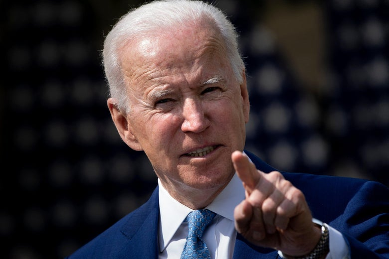 Joe Biden points while speaking from behind a podium in the Rose Garden of the White House.