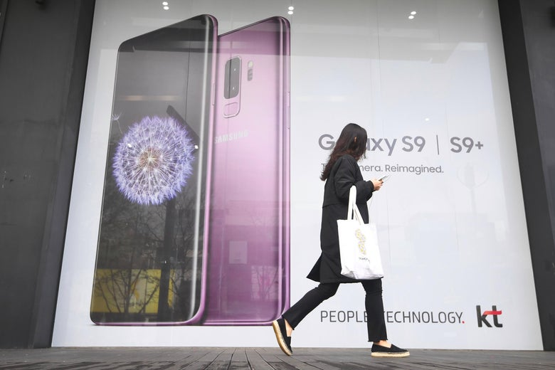 A woman walks past an advertisement for the Samsung Galaxy S9 at a mobile phone shop in Seoul.