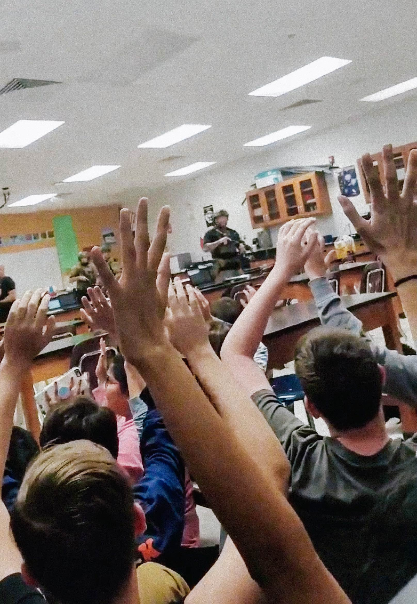 Students put their hands up in the air as armed police enter their classroom, following a shooting at the Marjory Stoneman Douglas High School in Parkland, Florida, in this screengrab taken from a Feb. 14 social media video.