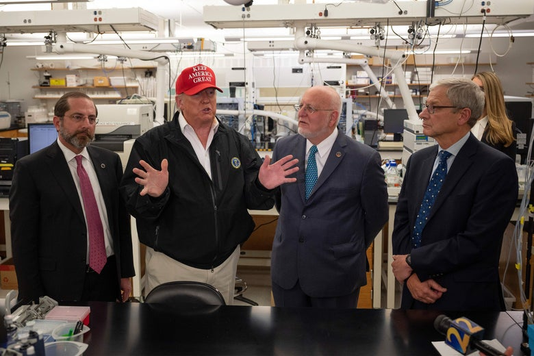 Azar, Trump, Redfield, and Monroe stand in a lab. Trump gestures with his hands and wears a MAGA hat.