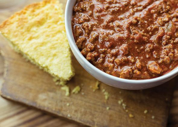 Bowl of chili with a piece of cornbread on a wooden background.