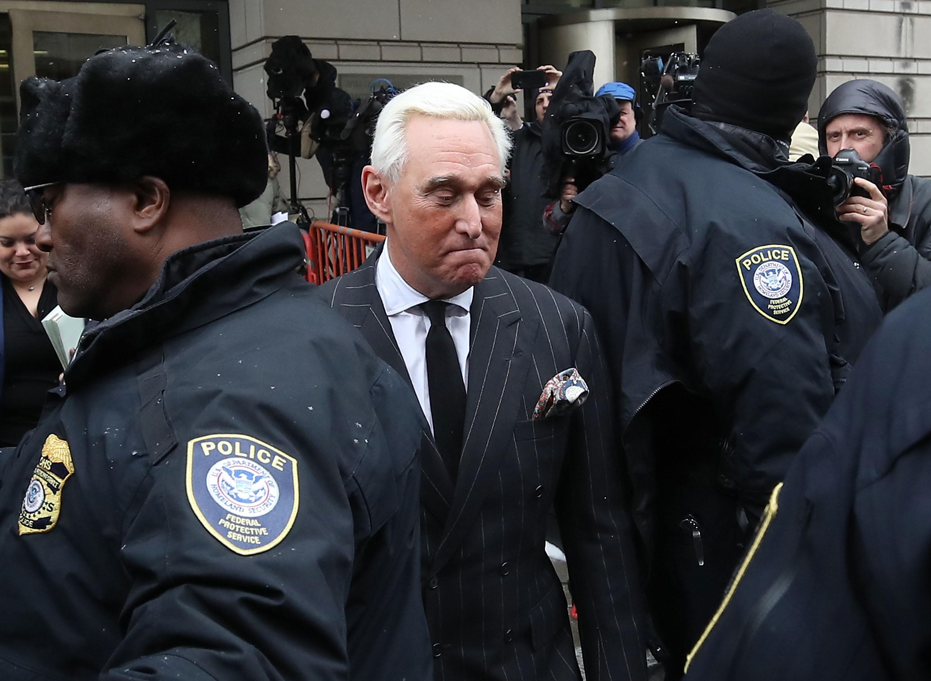 Roger Stone glances downward as he moves through a crowd of police and media in front of the courthouse.