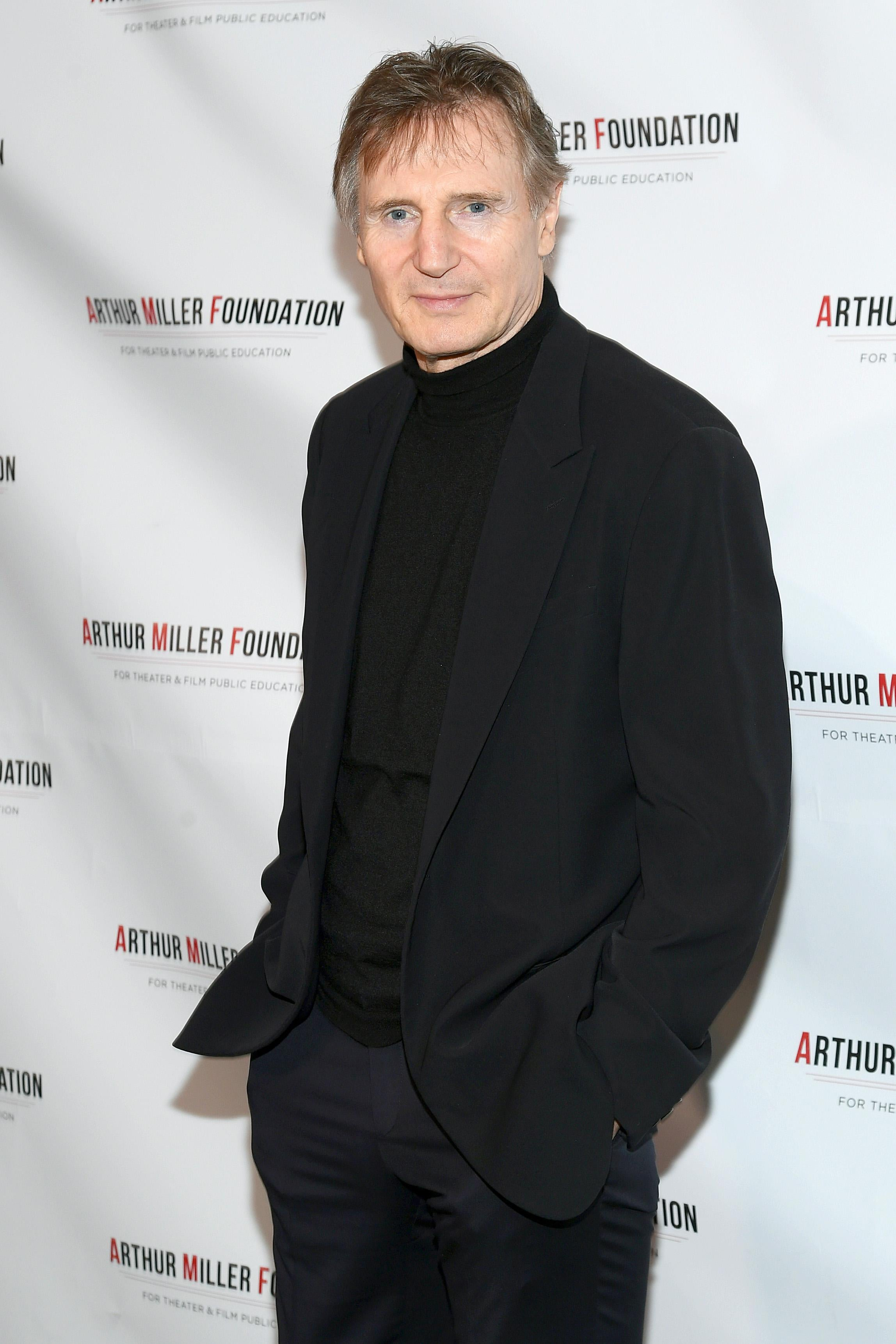 Man in black suit and black dress shirt poses for the camera.