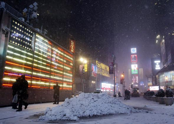People walk through Times Square during a snowstorm in New York January 26, 2011.