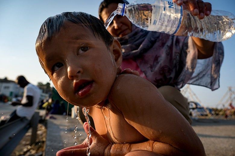 A woman pours water from a plastic water bottle onto a child.