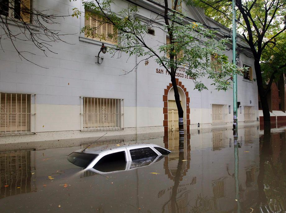 A submerged car is seen in a flooded street after a rainstorm in Buenos Aires on April 2, 2013.