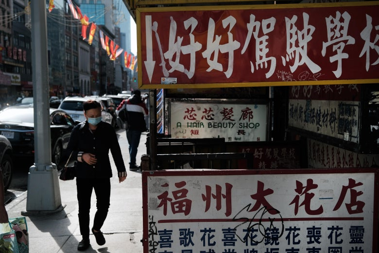 People walk on a sidewalk in Chinatown past signs in Chinese