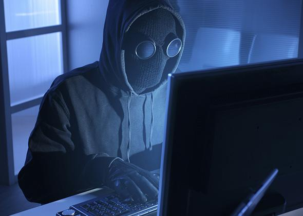 Anonymous man sitting in front of computer.
