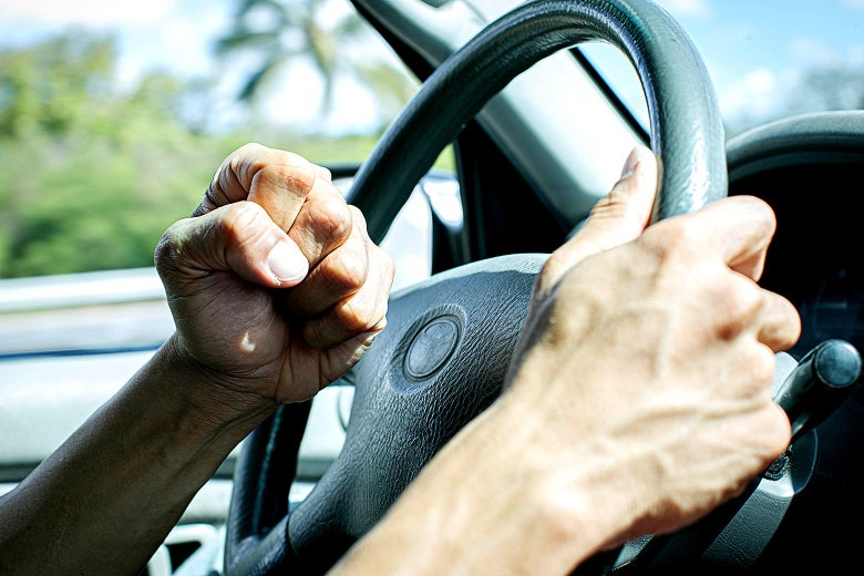 A frustrated driver holding a steering wheel w/ his right hand and a clenched left fist.
