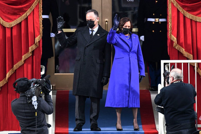 Doug Emhoff and Kamala Harris wave in front of the Capitol doors. Emhoff wears a dark suit, overcoat, and mask. Harris wears a purple coat with a purple dress underneath and a black mask.