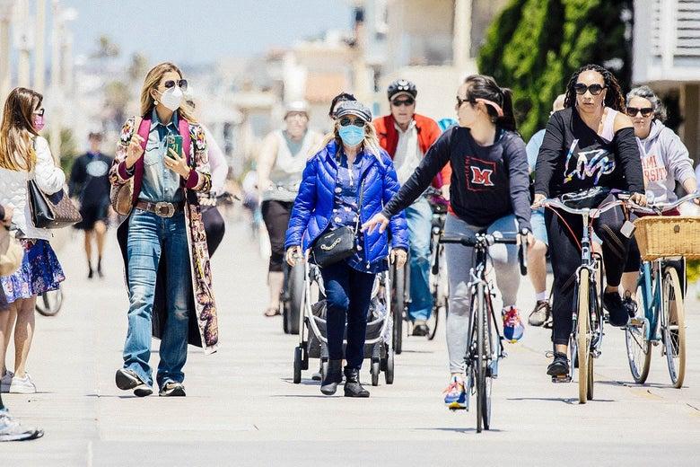 Masked and unmasked people biking and walking