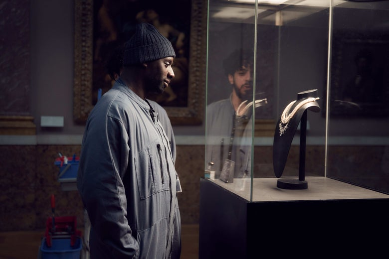Omar Sy stands in a dimly lit gallery, looking into a glass case containing a necklace.