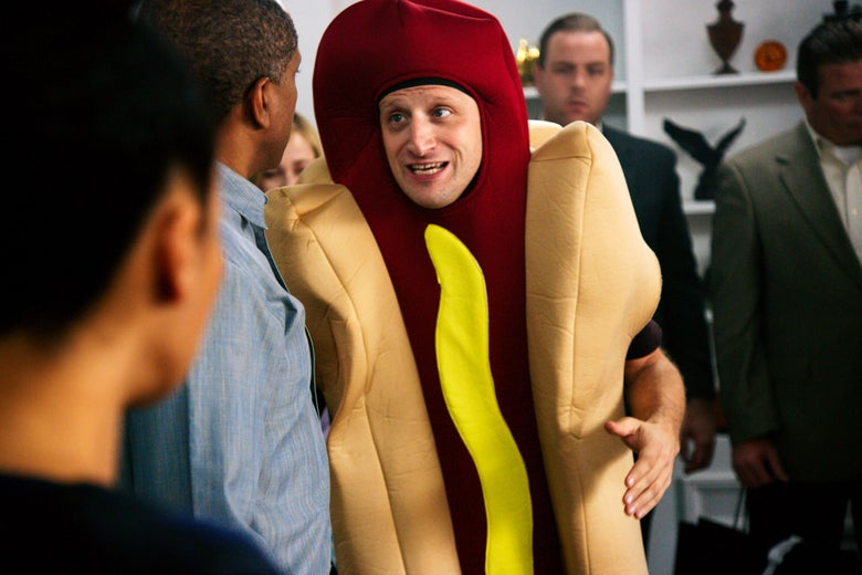 Tim Robinson stands in a crowd of people wearing a hot dog costume.