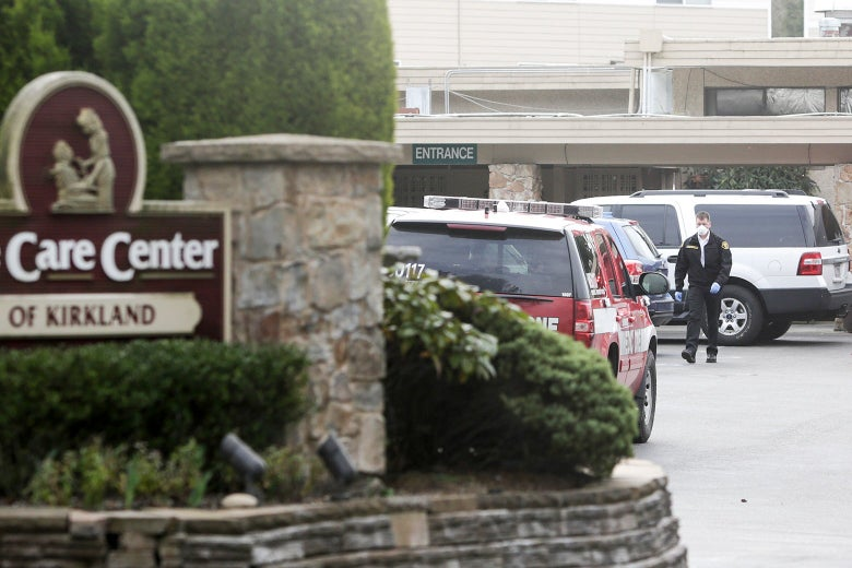 A Care Center sign is seen in front of a parking lot, where a man is walking besides some cars.