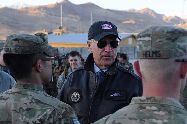 Biden in an American flag hat speaks to two soldiers with mountains and a helicopter in the background.