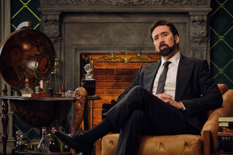 Nicolas Cage reclines in an armchair by a fire.