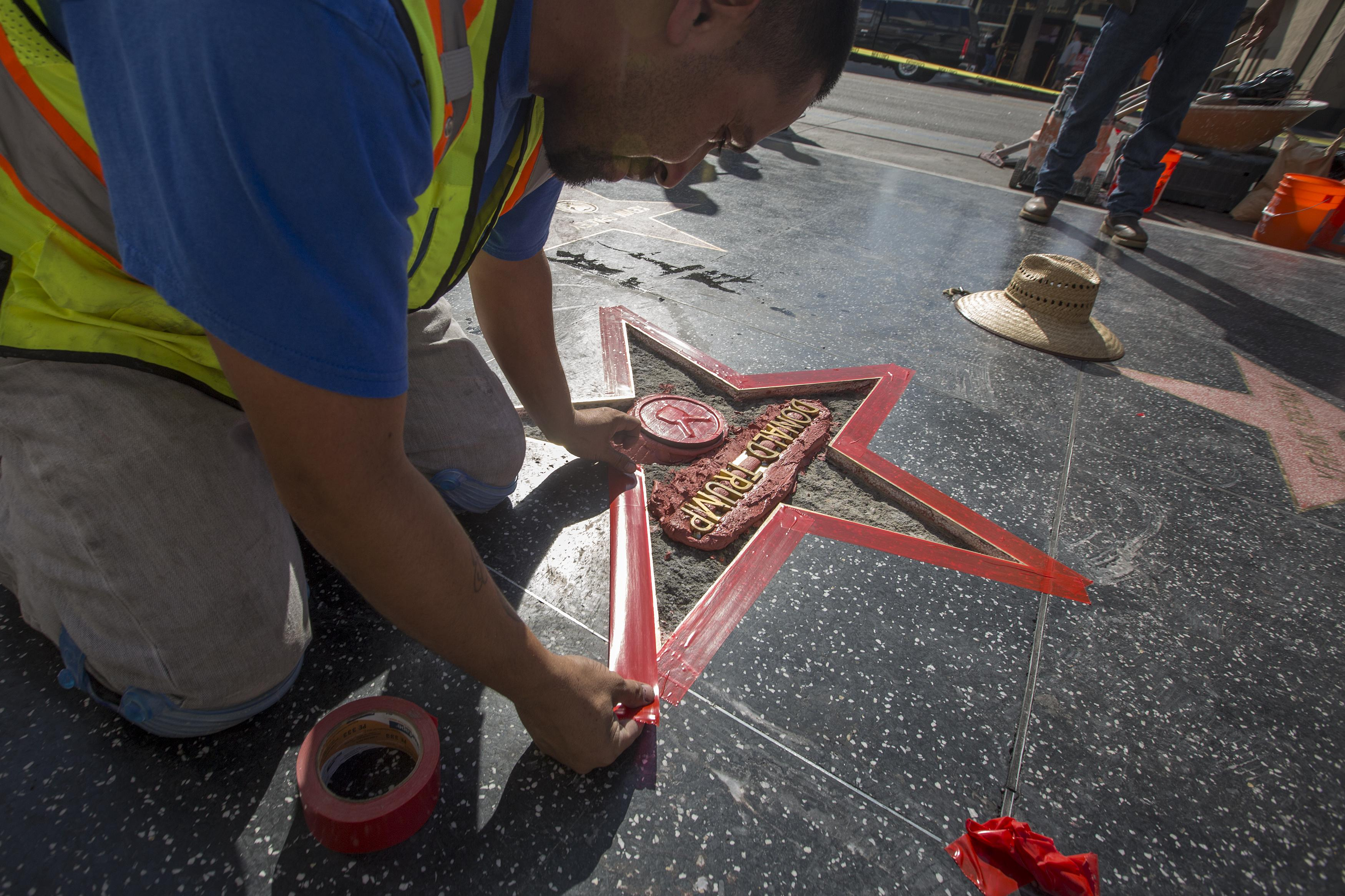 A worker repairs Donald Trump's star on the Walk of Fame.