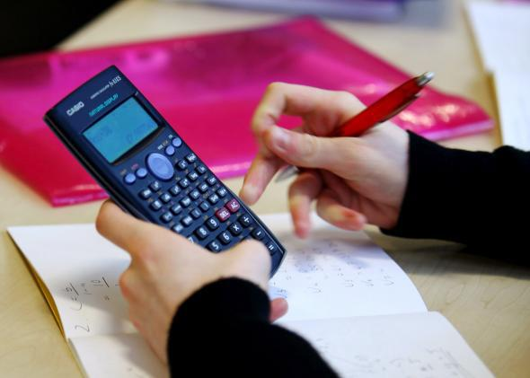 A high-school student uses a calculator.