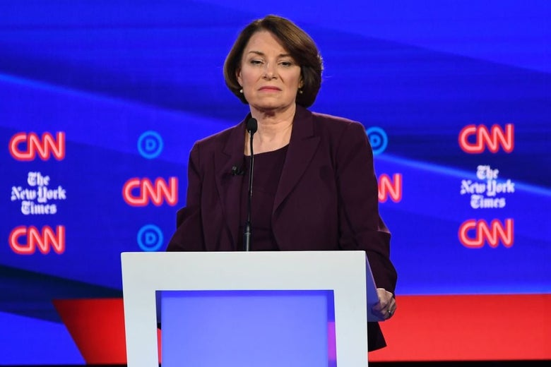 Amy Klobuchar frowns while holding a debate lectern.