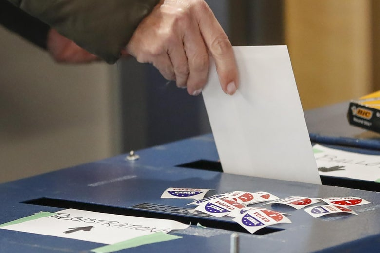 "A hand puts a ballot in a ballot box that has ""I Voted Early"" stickers on top of it"