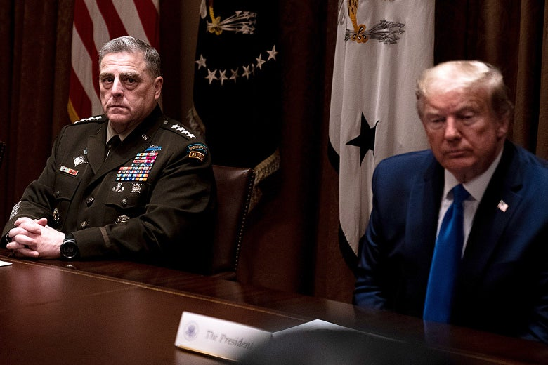 Mark Mille­y sits at a table with Trump. Milley's hands are folded on the table and he is in military uniform. Trump is wearing a suit.