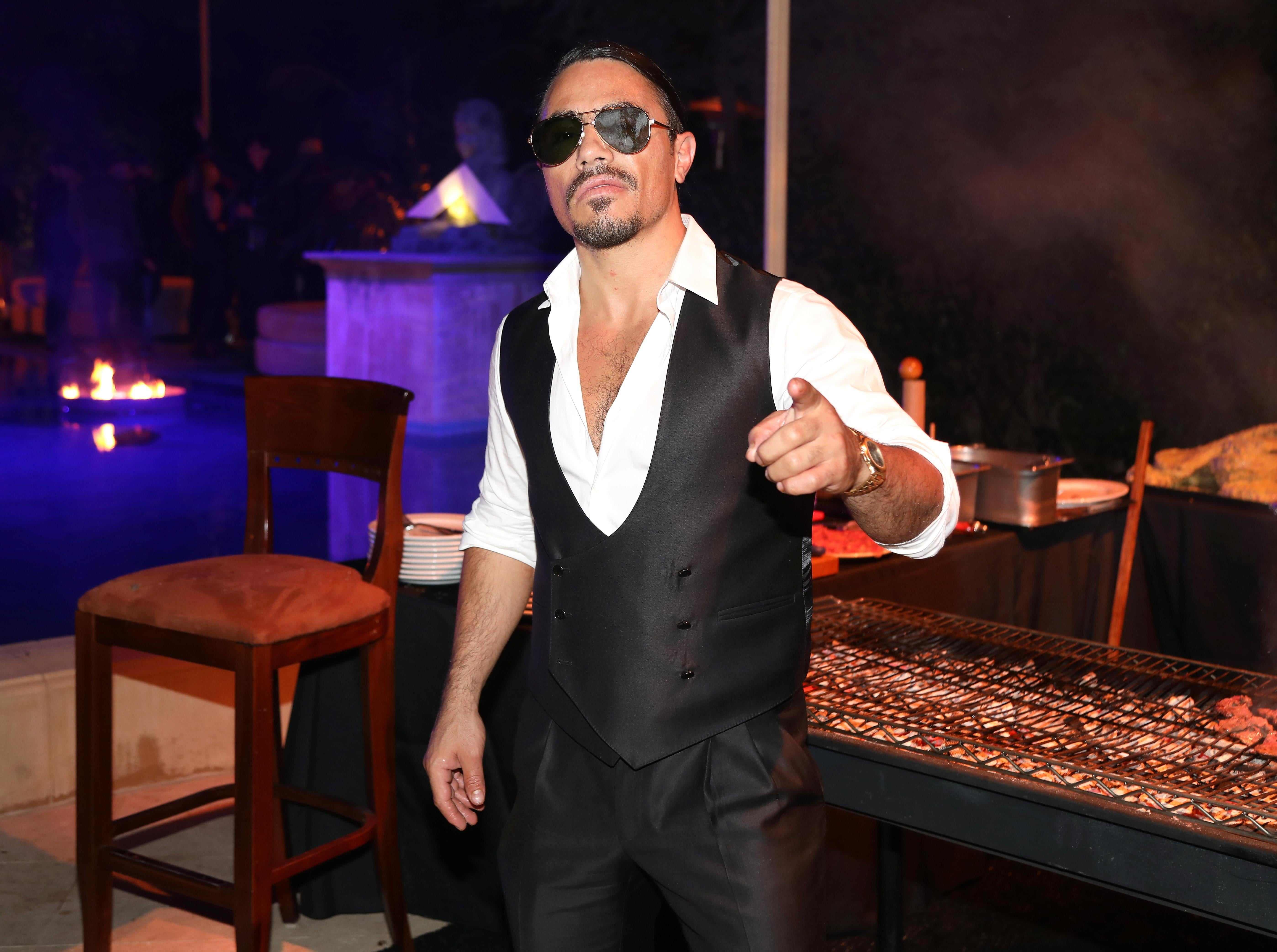 Nusret Gökçe, wearing a low-buttoned shirt and vest with sunglasses, points toward the camera while standing in front of a grill at a partylike setting.