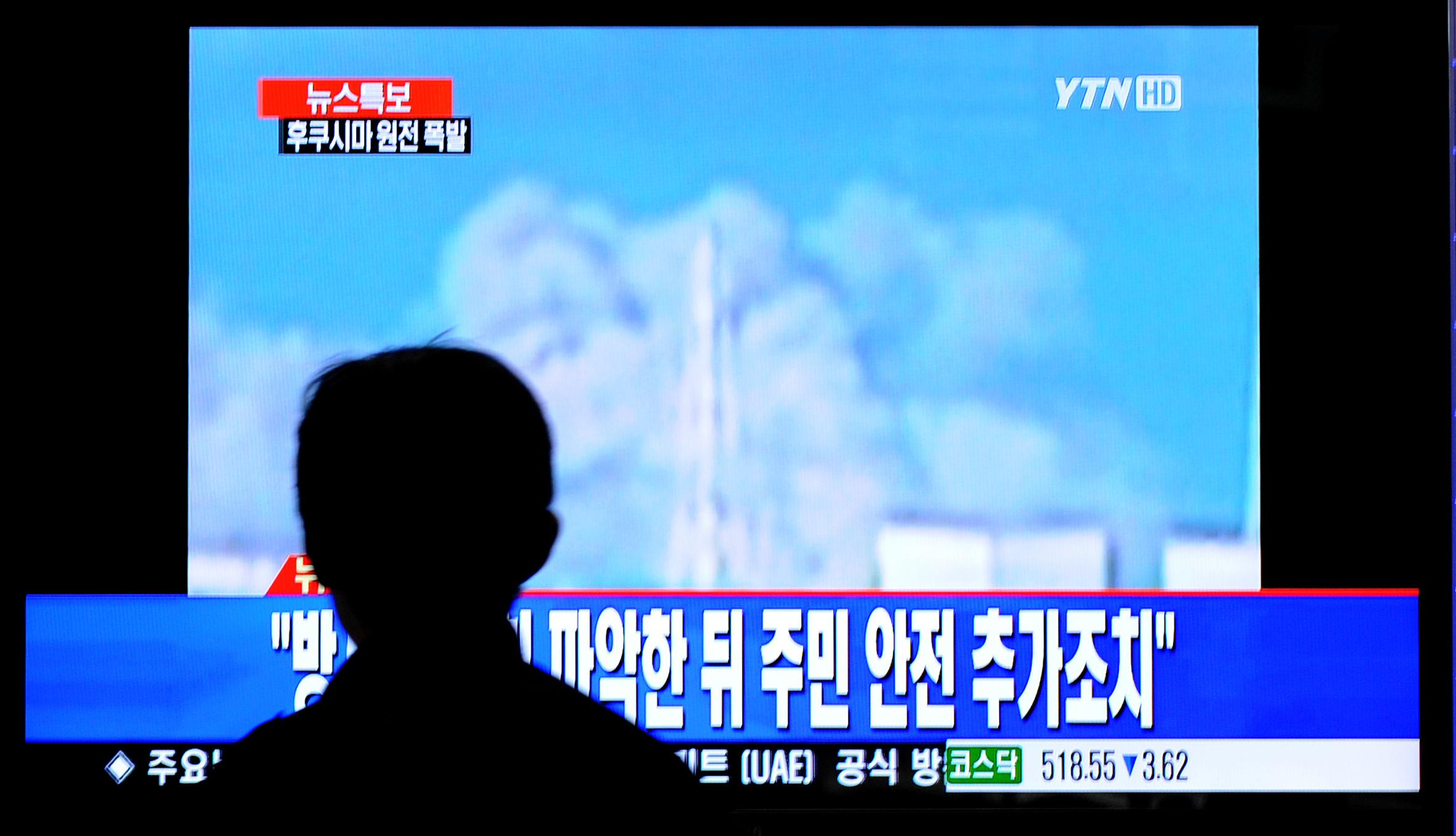A South Korean passenger watches TV showing Japan's Fukushima No. 1 atomic plant spewing fumes.