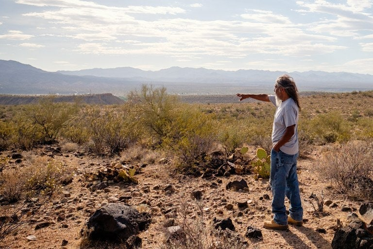 A man points out at a grassy field.