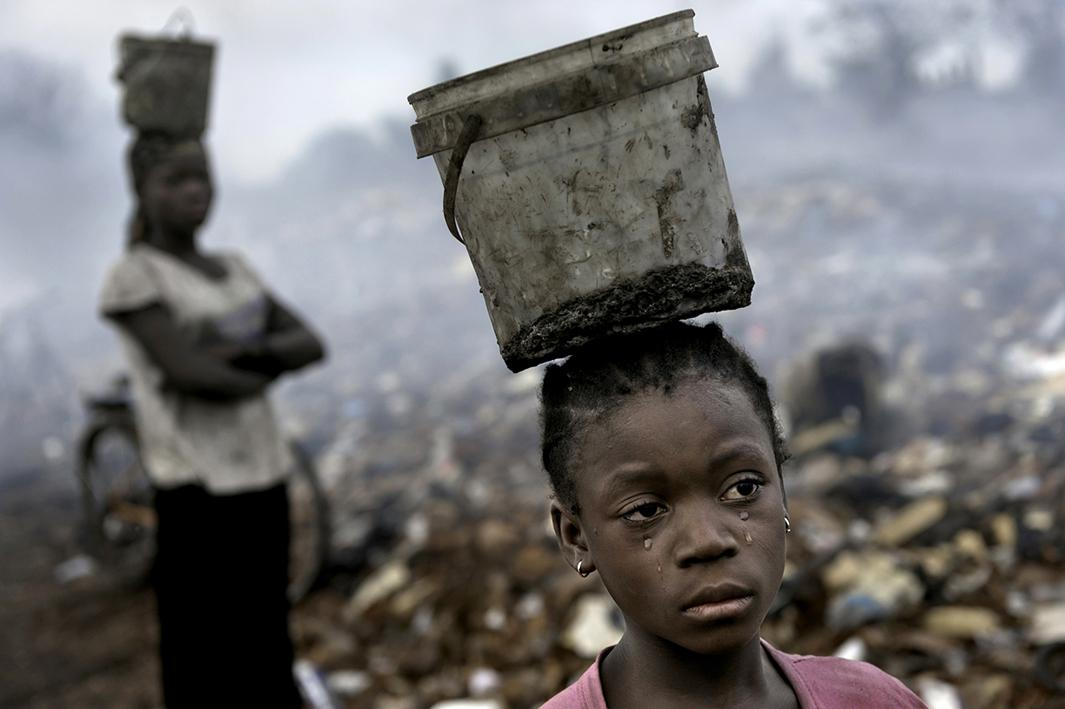 In an e-waste dump that kills nearly everything that it touches, Fati, 8, works with other children searching through hazardous waste in hopes of finding whatever she can to exchange for pennies in order to survive. While balancing a bucket on her head with the little metal she has found, tears stream down her face as the result of the pain that comes with the malaria she contracted some years ago. This is work she must do to survive.