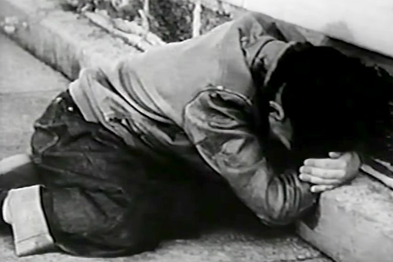 A child ducks under a desk in a still from the educational film Duck and Cover.
