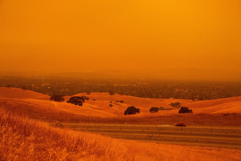 A car drives by in a landscape turned orange-red by wildfire smoke.