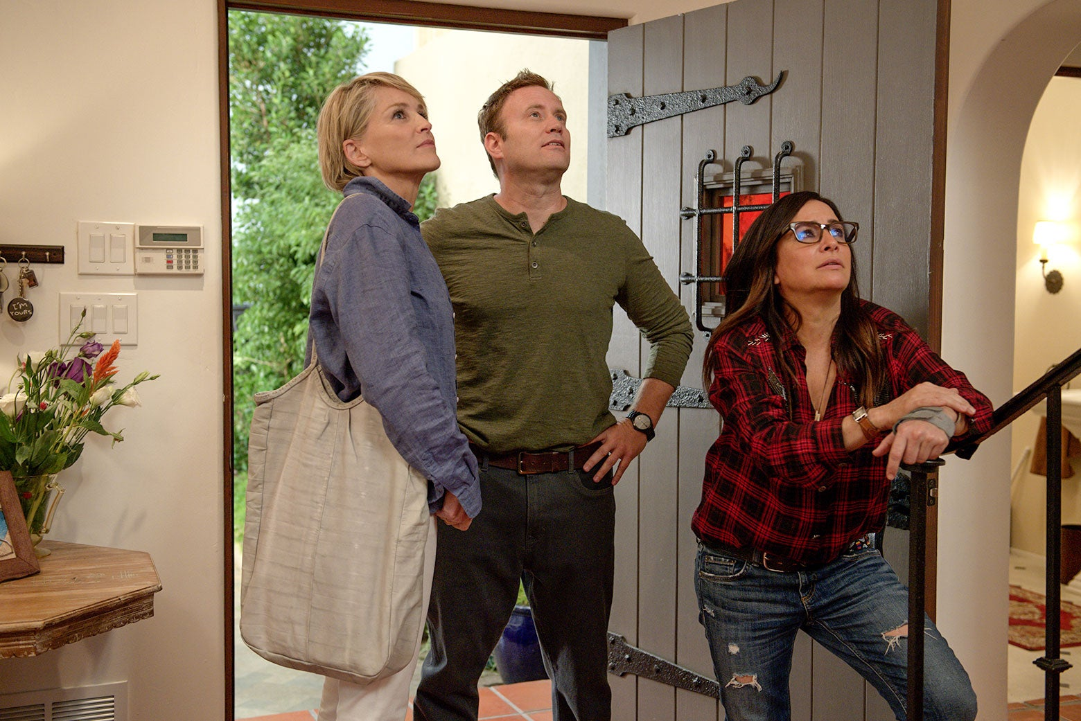 Sharon Stone, Greg Cromer and Pamela Adlon in a still from Better Things Season 3, Episode 3. They're all standing in a doorway looking off-camera; Adlon is leaning on a bannister.