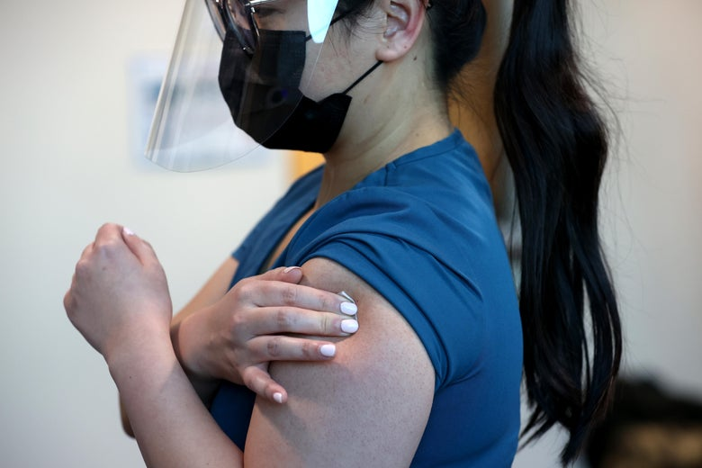 A woman in a face shield and mask presses her right fingertips against a bandage on her left arm.