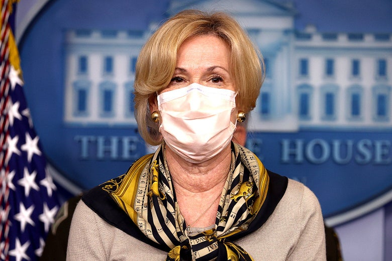 Birx wearing a mask and a scarf, standing in front of the White House logo in the press briefing room