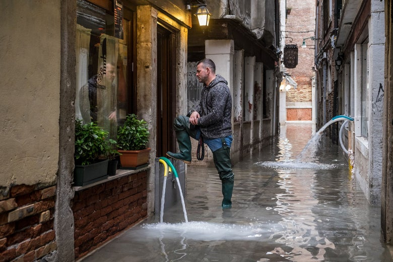 A man staring at his restaurant damaged by flooding, in Venice.