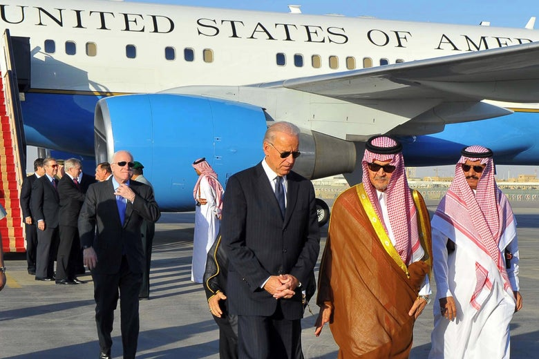 Biden speaks with two Saudi officials on the tarmac while walking away form Air Force II.