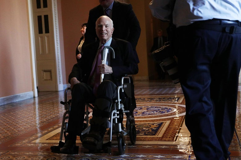 Sen. John McCain (R-AZ) passes by on a wheelchair in a hallway at the Capitol December 1, 2017 in Washington, D.C.