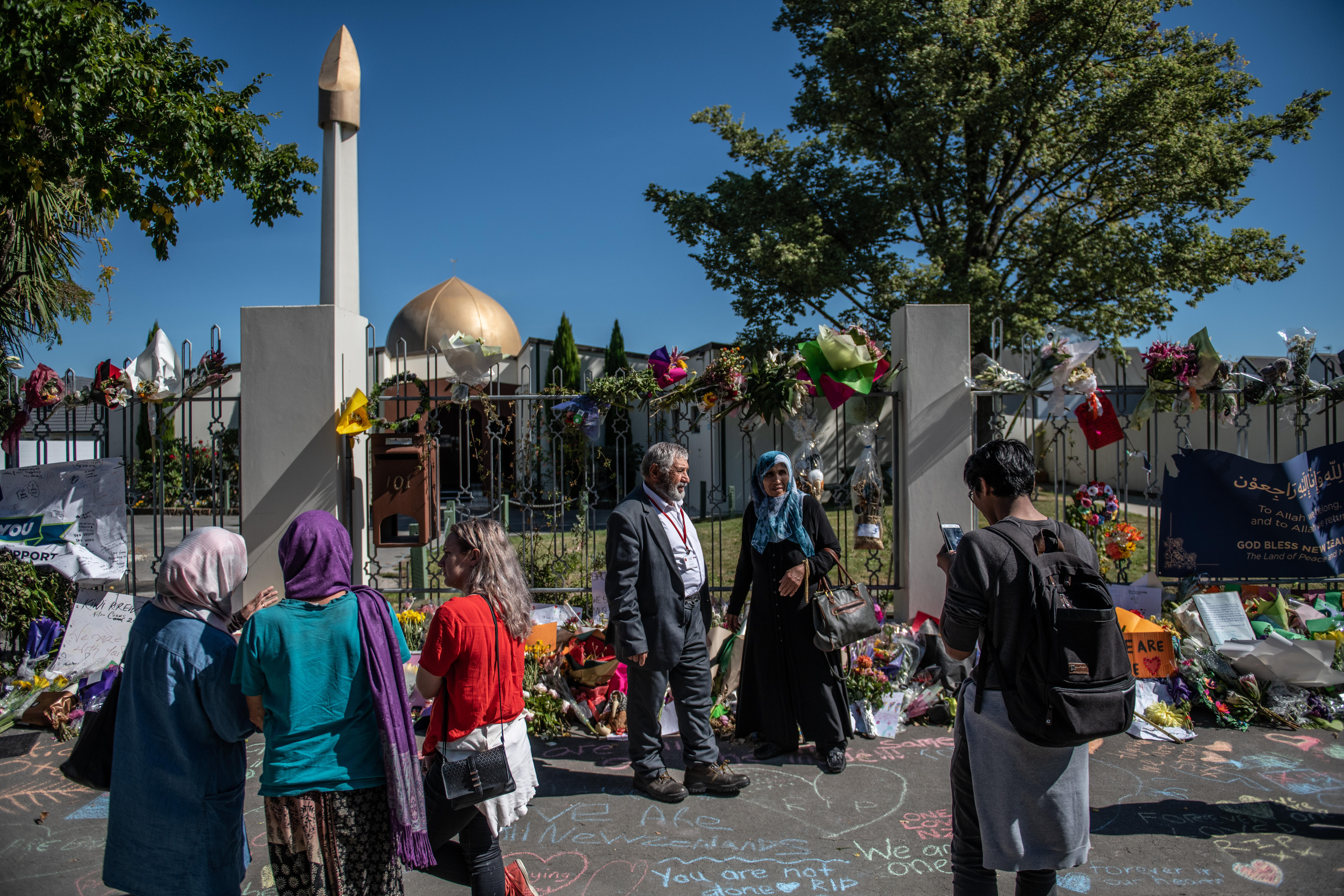 People stand outside the mosque, next to many flowers placed in tribute to the victims of the March 15 attacks.