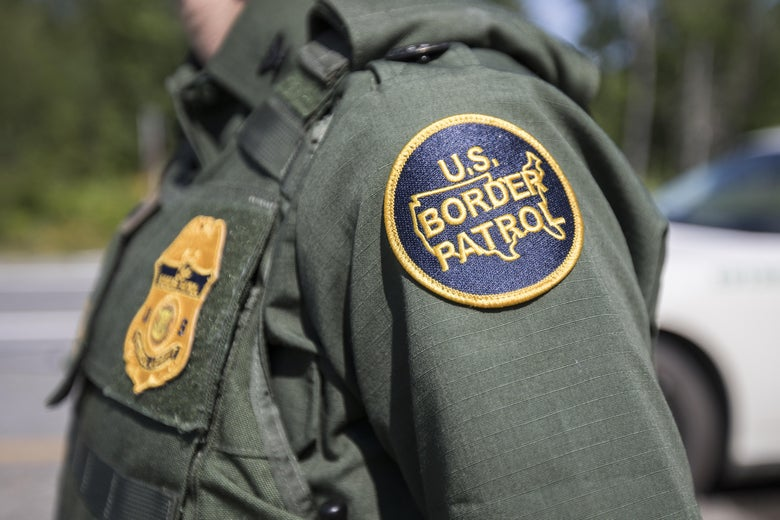 The shoulder of a Border Patrol agent is seen, with the institution's patch prominently displayed.