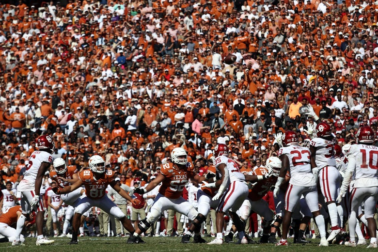A scrum of Texas and Oklahoma players on the football field with the crowd in Texas orange and Oklahoma red looking on in the background