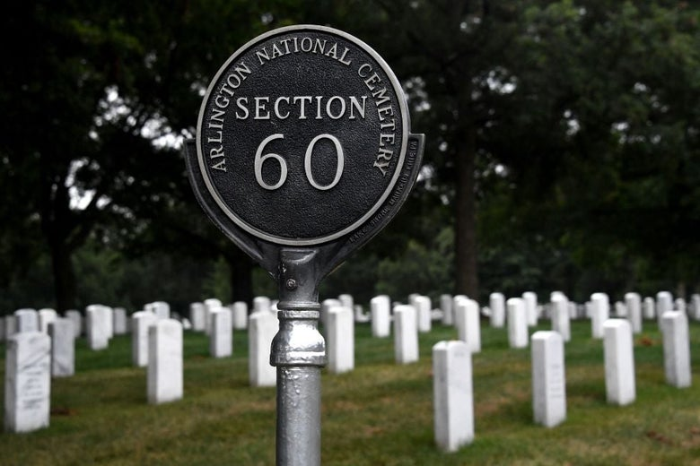 """Rows of white headstones stand behind a sign that reads, """"Arlington National Cemetery: Section 60."""""""