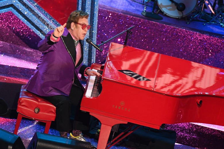 A man with brown hair and purple sunglasses wears a purple suit while performing on stage. He is playing a bright red piano, and there are sparkly purple-and-gold decorations behind him.