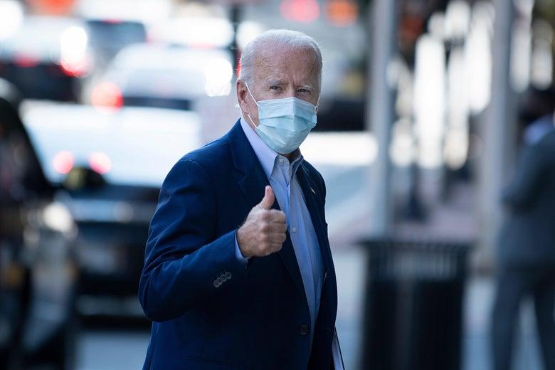 Joe Biden, wearing a mask, gives a thumbs-up as he walks
