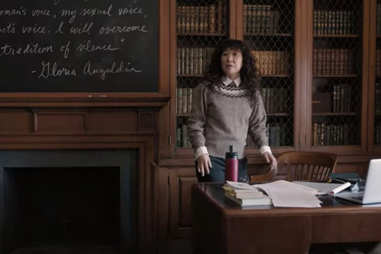 Dr. Kim stands at the front of a grand-looking college classroom with bookshelves and a blackboard behind her.