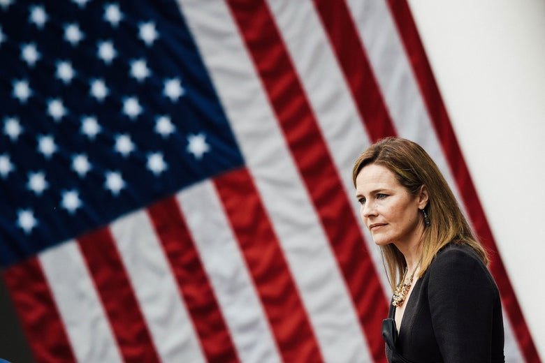 Amy Coney Barrett in profile in front of an American flag.