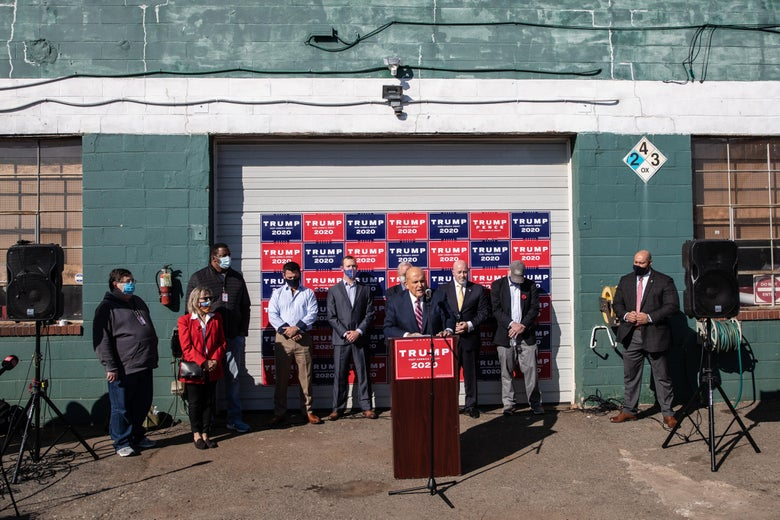 Rudy Giuliani speaks at a Trump 2020–branded lectern in front of crowd gathered in front of a garage plastered with Trump signs.