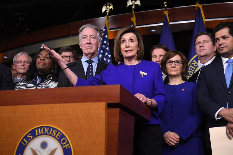 Nancy Pelosi, surrounded by other congressional leaders, speaks at a lectern.