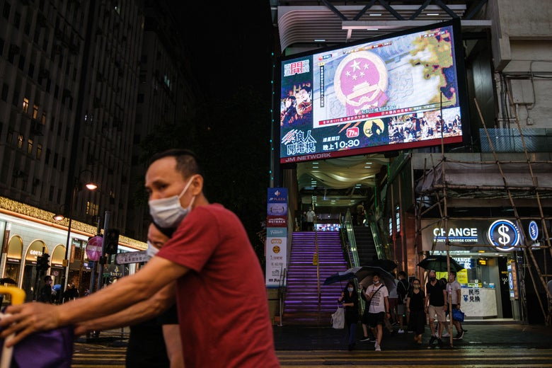 Pedestrians walk under a television screen in Hong Kong on May 21, 2020, showing a news broadcast from Beijing of the National Emblem of the People's Republic of China, ahead of the National People's Congress that opens on May 22.