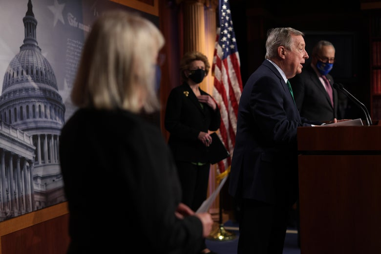 Dick Durbin speaks from a podium while colleagues stand spaced out around him.
